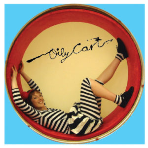 Circular image with blue border. Performer in black and white striped costume lays inside a circular drum. The Oily Cart logo is above her.