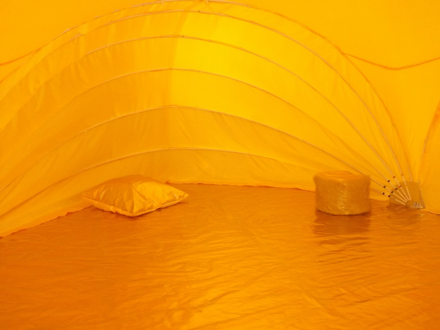 Image inside a golden fabric tent, with a golden cushion and stool.