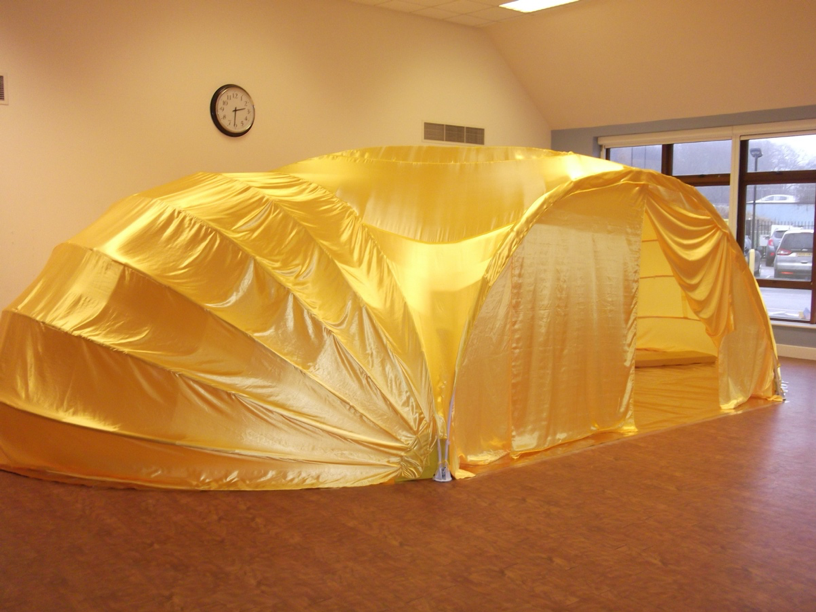 Image of large golden fabric tent inside a school hall.