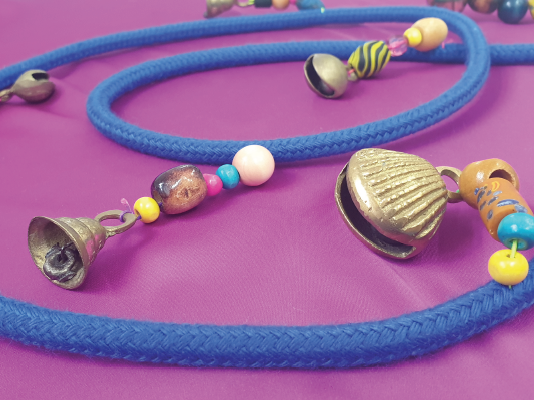 Blue rope with colourful beads and bells hanging from it, laid on pink fabric.