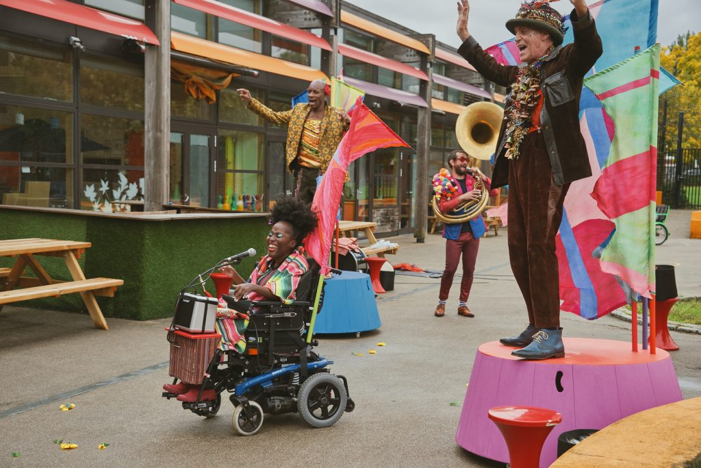 Four members of the band performing in a playground. Two of the band members stand on colourful podiums with their arms raised in the air. The singer is in a wheelchair infront of them, and a sousaphone player behind them. They are all wearing colourful festival costumes and smiling at the audience who are out of shot. Photo from Doorstep Jamboree, credit Suzi Corker