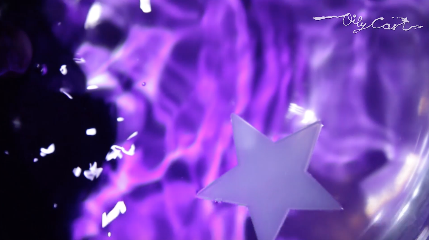 A purple star floating in purple coloured water. The Oily Cart logo is in the top right corner.