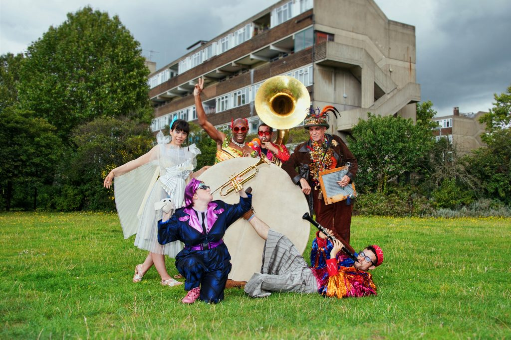 Photograph of the Jamboree band in a field. They are all wearing colourful, festival outfits and holding their instruments. They are stood around a huge drum. In the background are trees and a block of flats. Photo from Jamboree, credit Suzi Corker