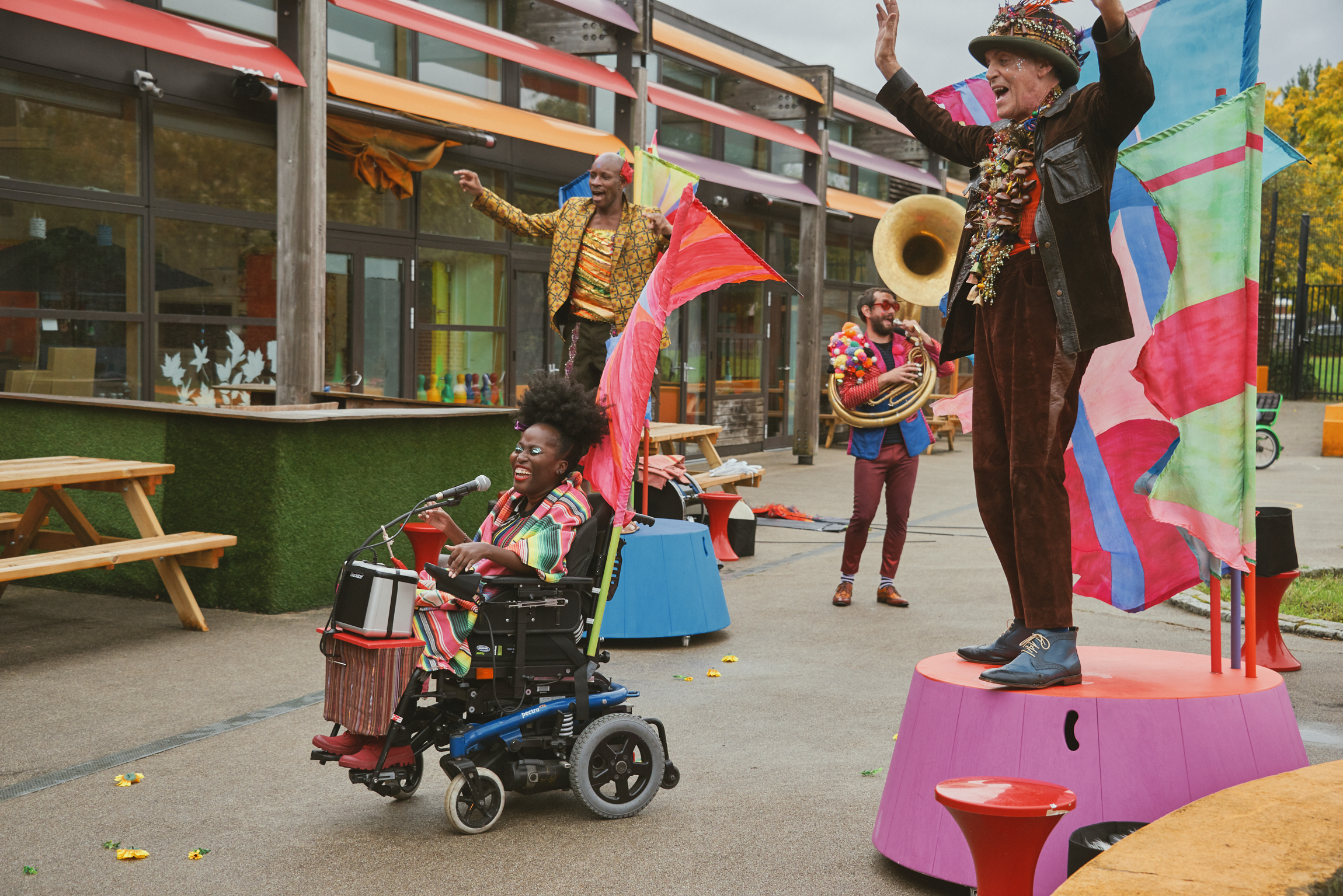 Four members of the band performing in a playground. Two of the band members stand on colourful podiums with their arms raised in the air. The singer is in a wheelchair infront of them, and a sousaphone player behind them. They are all wearing colourful festival costumes and smiling at the audience who are out of shot. Photo from Doorstep Jamboree,credit Suzi Corker