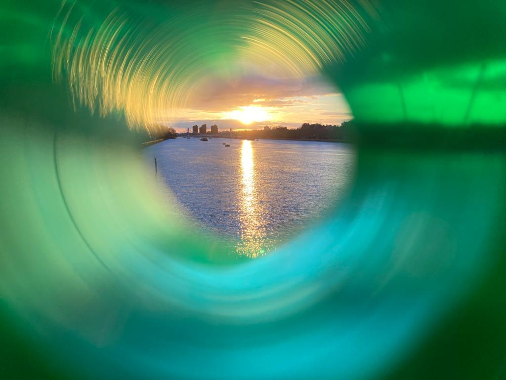 View through a green straw of a sunset over a river with a cityscape