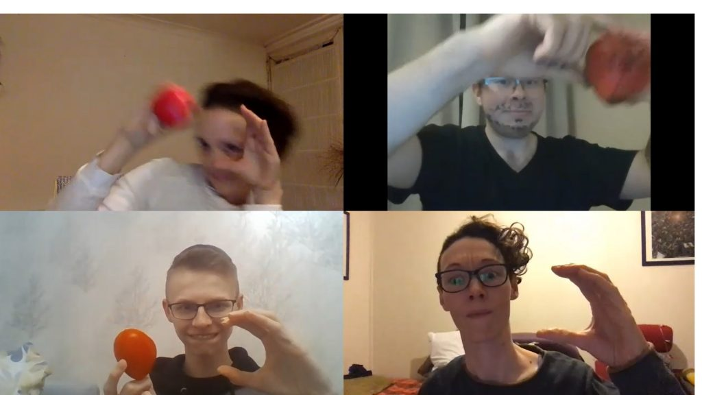 Zoom screen with four participants, all holding up a red squishy heart.